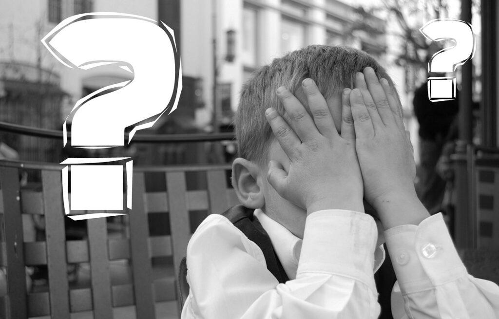 Niño pequeño lamentando un error cubriendo su rostro
